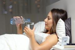Agua potable de la mujer en la cama en la noche Imagenes de archivo