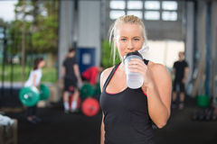 Agua potable de la mujer en el centro del gimnasio de la aptitud imágenes de archivo libres de regalías