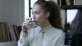 Agua potable de la mujer en el vidrio, sentándose en oficina, jóvenes,