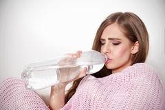 Agua potable de la mujer enferma hermosa Imagen de archivo