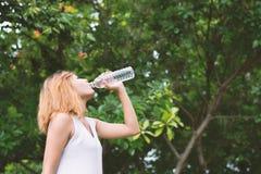 Agua potable de la mujer hermosa joven en el parque verde Fotos de archivo libres de regalías
