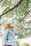 Agua potable de la mujer hermosa joven de la vida de la mujer en el parque verde Foto de archivo