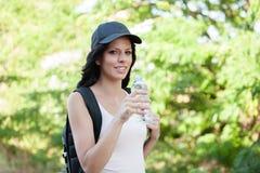Agua potable de la mujer hermosa mientras que camina Foto de archivo libre de regalías