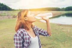 Agua potable de la mujer joven del inconformista en el parque del verde del verano Imagen de archivo