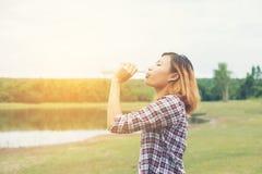 Agua potable de la mujer joven del inconformista en el parque del verde del verano Foto de archivo