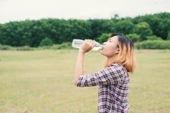 Agua potable de la mujer joven del inconformista en el parque del verde del verano Imágenes de archivo libres de regalías