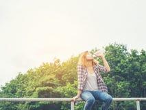 Agua potable de la mujer joven del inconformista en el parque del verde del verano Fotos de archivo