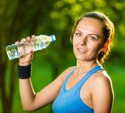 Agua potable de la mujer joven después del ejercicio de la aptitud Imagenes de archivo