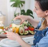 Agua potable de la mujer joven en la tabla con las verduras imagen de archivo libre de regalías