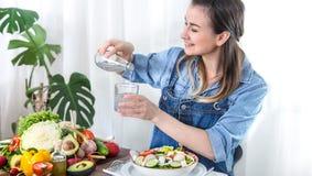 Agua potable de la mujer joven en la tabla con las verduras foto de archivo