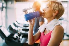 Agua potable de la mujer madura en gimnasio después del entrenamiento fotos de archivo libres de regalías