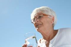 Agua potable de la mujer mayor imagen de archivo