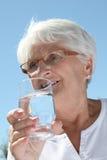 Agua potable de la mujer mayor fotos de archivo