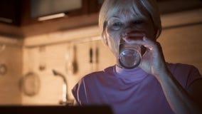 Agua potable de la mujer mayor del vidrio mientras que usa el ordenador portátil Freelancer en el trabajo nocturno de Ministerio  metrajes
