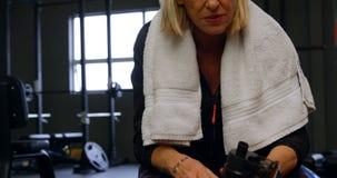 Agua potable de la mujer mayor en el estudio 4k de la aptitud almacen de metraje de vídeo