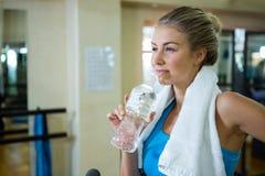 Agua potable de la mujer pensativa después del entrenamiento Fotografía de archivo libre de regalías