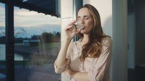 Agua potable de la mujer relajada cerca de la ventana panorámica Agua potable de la señora sedienta metrajes