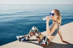 Agua potable de la mujer rubia joven de la aptitud después de correr en la playa fotos de archivo libres de regalías