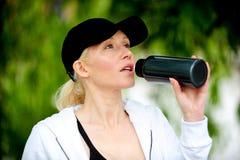 Agua potable de la mujer rubia sana del ajuste Imagen de archivo