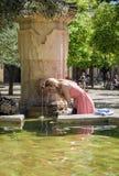 Agua potable de la mujer y enfriamiento de una fuente al día caliente en cordón Fotos de archivo