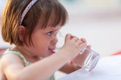 Agua potable de la niña al aire libre Imágenes de archivo libres de regalías