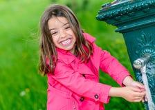 Agua potable de la niña en una fuente Imágenes de archivo libres de regalías