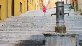 Agua potable de la pequeña muchacha adorable del golpecito afuera en el día de verano caliente en Roma, Italia metrajes