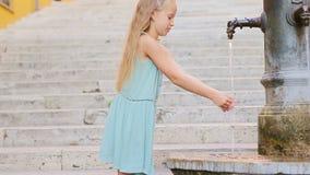 Agua potable de la pequeña muchacha adorable del golpecito afuera en el día de verano caliente en Roma, Italia almacen de metraje de vídeo
