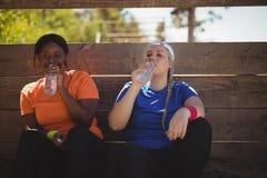 Agua potable de los amigos después del entrenamiento durante carrera de obstáculos Fotos de archivo