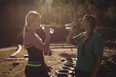 Agua potable de los amigos después del entrenamiento durante carrera de obstáculos Imágenes de archivo libres de regalías