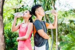 Agua potable de los pares asiáticos después del deporte en parque Imagenes de archivo