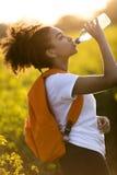 Agua potable del adolescente afroamericano de la muchacha de la raza mixta en los soles Imagenes de archivo