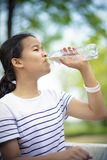 Agua potable del adolescente asiático de la botella plástica Imágenes de archivo libres de regalías