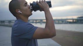 Agua potable del atleta afroamericano durante entrenamiento de funcionamiento almacen de video
