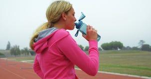 Agua potable del atleta de sexo femenino en el circuito de carreras 4k almacen de video