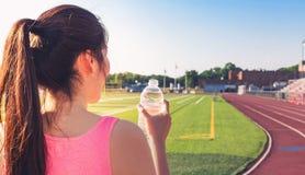 Agua potable del atleta de sexo femenino en una pista corriente Fotografía de archivo