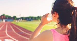 Agua potable del atleta de sexo femenino en una pista corriente Imágenes de archivo libres de regalías