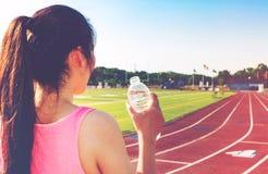 Agua potable del atleta de sexo femenino en una pista corriente Foto de archivo libre de regalías
