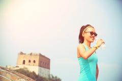 Agua potable del atleta del corredor de la mujer en la Gran Muralla china Imagenes de archivo