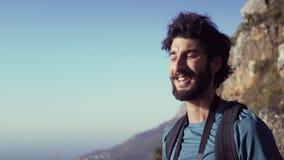 Agua potable del caminante feliz mientras que se opone en la montaña al cielo almacen de video