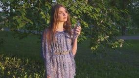 Agua potable del caminante femenino hermoso en bosque en la puesta del sol Una muchacha en un vestido bebe el agua fresca de una  almacen de video