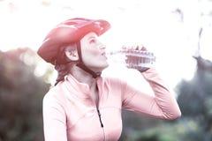 Agua potable del ciclista femenino en bosque Imágenes de archivo libres de regalías