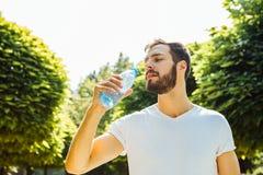 Agua potable del hombre adulto de una botella afuera imagen de archivo libre de regalías