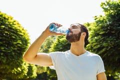 Agua potable del hombre adulto de una botella afuera foto de archivo
