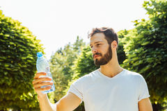Agua potable del hombre adulto de una botella afuera imágenes de archivo libres de regalías
