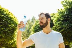Agua potable del hombre adulto de una botella afuera imagenes de archivo