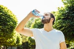 Agua potable del hombre adulto de una botella afuera fotografía de archivo