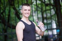 Agua potable del hombre hermoso del atleta Foto de archivo