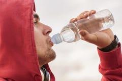 Agua potable del hombre joven Foto de archivo