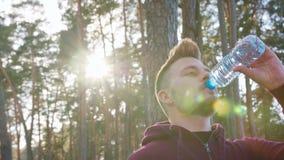 Agua potable del hombre joven en el bosque almacen de video